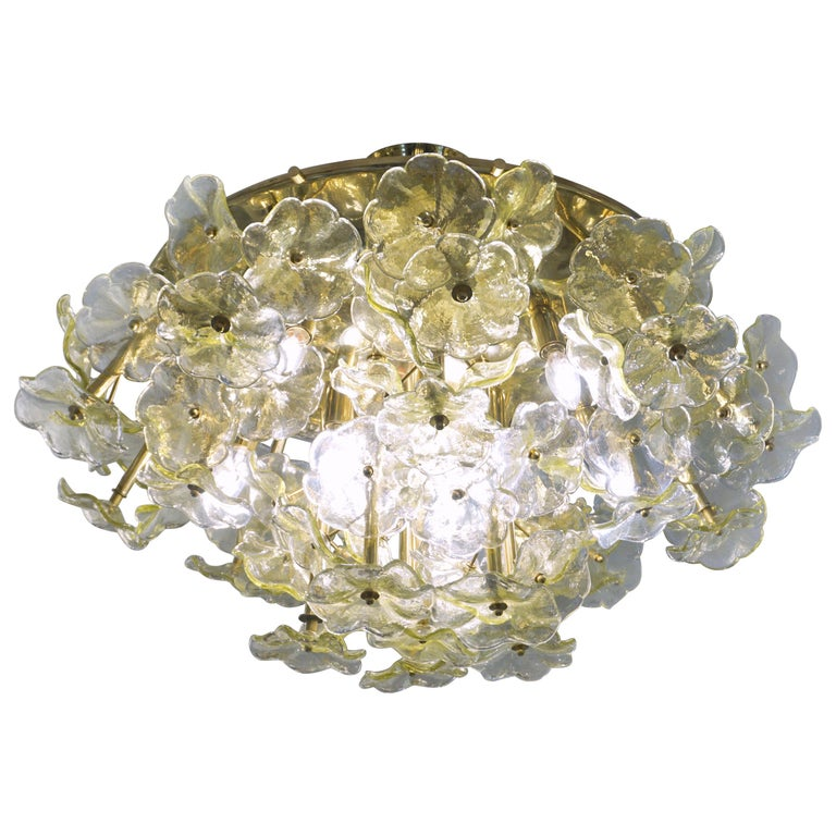 1970s Italian one-of-a-kind amber yellow Murano glass flower chandelier, organic modern design entirely handcrafted in Italy, the round convex structure in brass that can be mounted nearly flush is artistically and uniquely decorated with a cluster