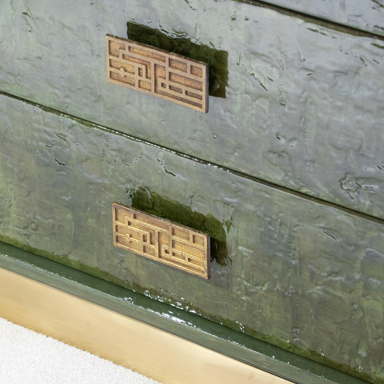 1970s Italian vintage chest of drawers in perfect condition newly covered with overlapping epoxy resin and colored pigments to create an enameled ceramic effect surface in camouflage green, original forged bronze handles, natural brass base.