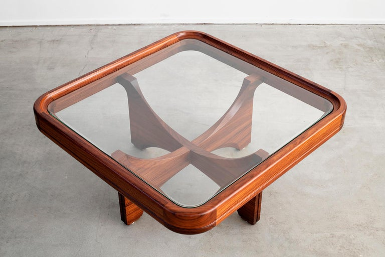 Beautiful Italian glass and walnut coffee table with curved corners and floating sculptural legs.