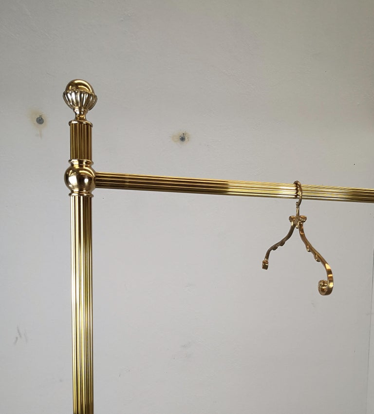 Vintage 1970s Italian stylish and shiny brass hanger stand, with Classic carved column and decorated top finals, standing on 4 brass covered wheels. A great piece that perfectly adds to every shop, showroom or home decor the typical glitz, glamour,
