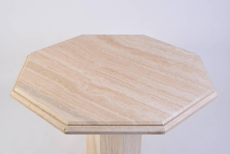 An octagonal travertine dining table