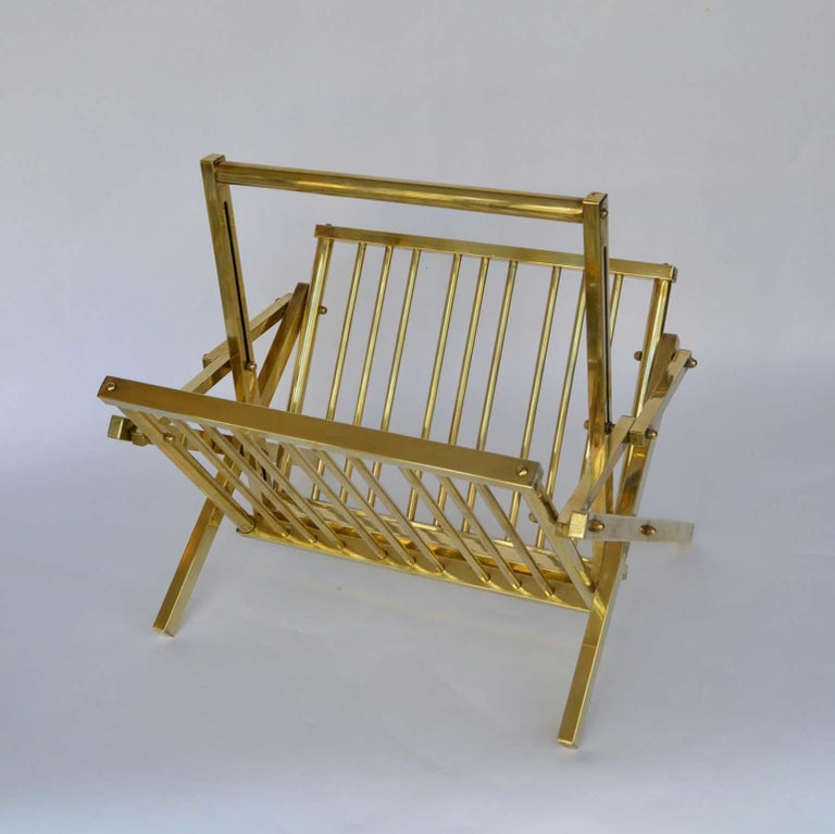 Stylish midcentury magazine rack in polished tubular brass.  It is collapsable, when folded it measures 49x42x6 cm.