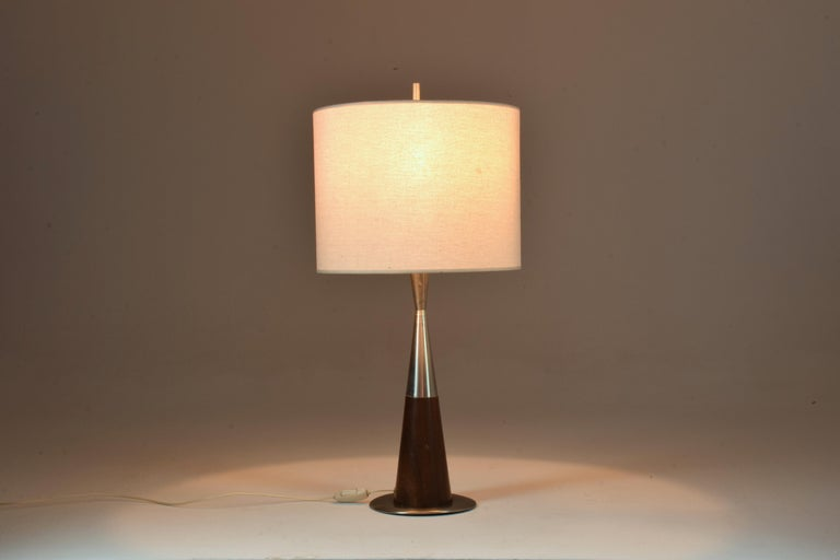 A 20th-century tall vintage table lamp designed in a stainless steel mix solid mahogany structure.  In fully restored condition with a new fabric cylinder shade. Labeled.  Italy. 1970's    We are an exhibition space and an online destination