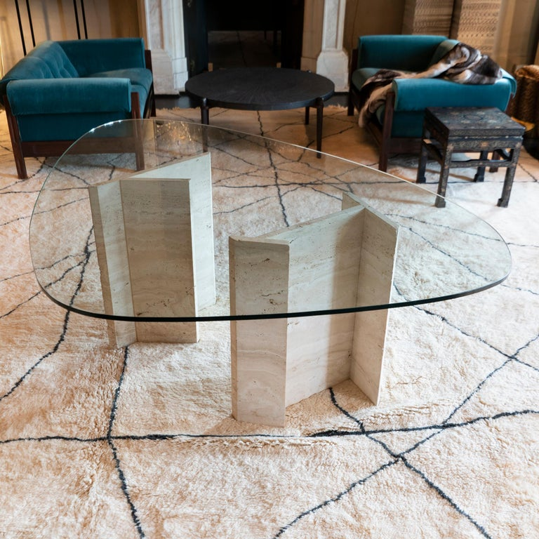 Sculptural center table with geometrical travertine bases in perfect condition and vintage patina, some chipping on both bases as showed, heavily scratched surface oval shape glass top, Italy, circa 1970.