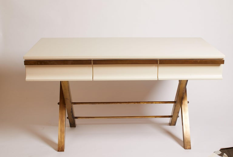 Italian white lacquer desk featuring brass legs and brass details on drawers, circa 1970.