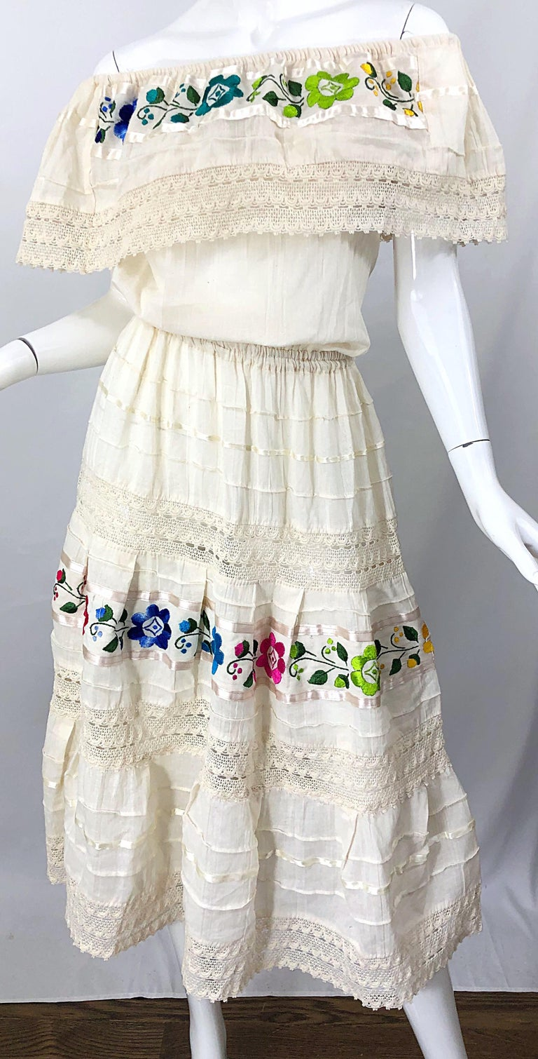 Chic 70s ivory cotton embroidered flowers off-the-shoulder boho Spanish inspired dress! Features a flattering relaxed fit bodice with elastic at the shoulders and waist. Bright colorful flowers of purple, blue, green, pink, yellow and turquoise