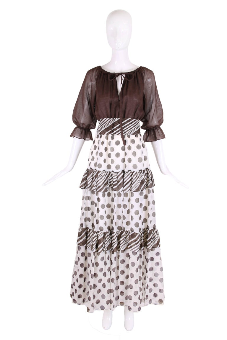 1970's Jack Bryan maxi dress with brown peasant style bodice w/keyhole opening that closes with ties at bodice front and a tiered polka dot maxi skirt with ruffle trim from striped fabric. Comes with detachable plaid sash that ties at the waist and
