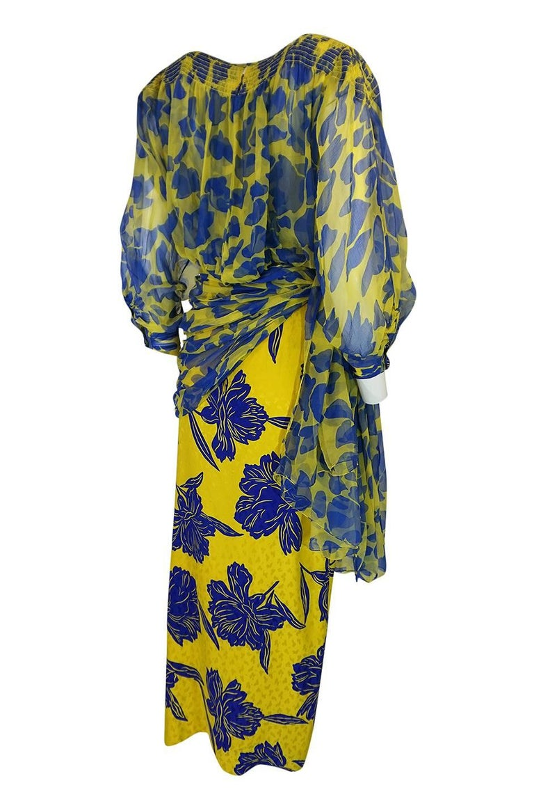 This unusual and striking Galanos dress dates to the late 1970s, early 1980s, and combines a silk twill with silk chiffon to create the layered print effect that you see. The entire dress is done in a combination of yellow and blue. The inner layer