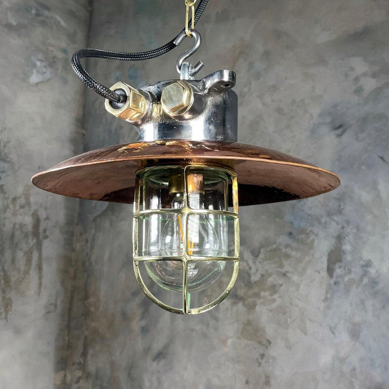 A reclaimed vintage Industrial explosion proof iron and copper cage light ceiling pendant. A solid metal light fixture with timeless design appeal.  Originally made in Japan and salvaged from 1970s cargo ships.   Professionally restored by hand