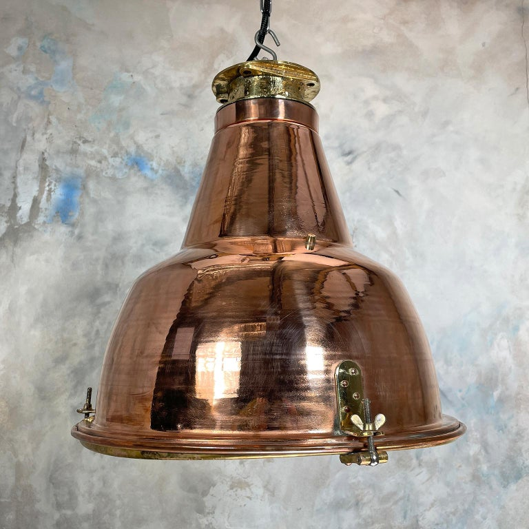 A large copper and brass pendant lamp made in Japan in the 1970s for industrial use on cargo ships and sea going vessels.   The dome is made from spun brass with a cast brass top, the lamp is accessed by unscrewing the wing nuts and opening the
