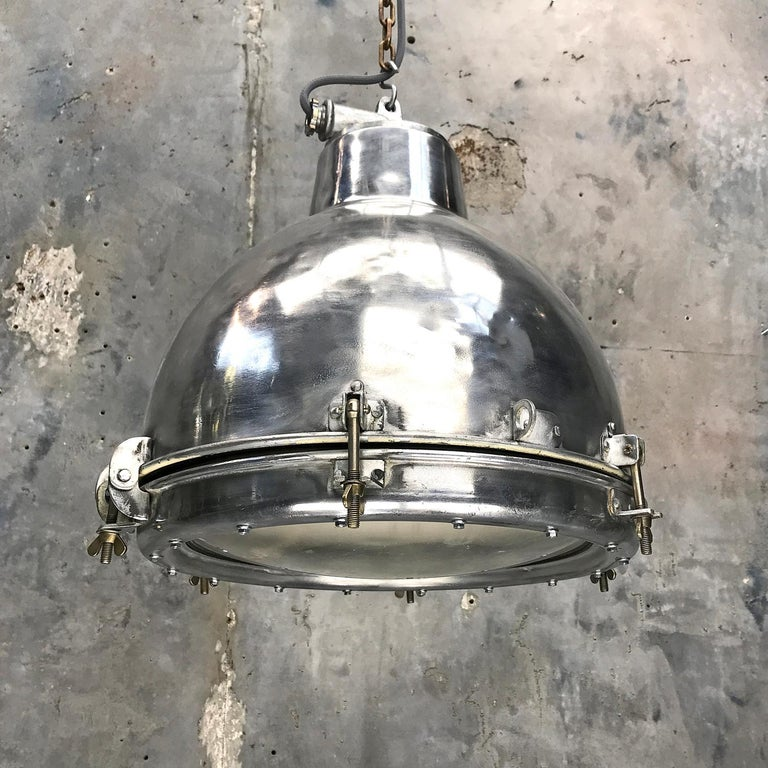 Polished aluminium dome pendant with toughenedconvex glass lens.  Originally used on super tankers and cargo ships built during the 1970s and were manufactured to IP65 standards.  The heavy convex glass opens the beam for a wider light