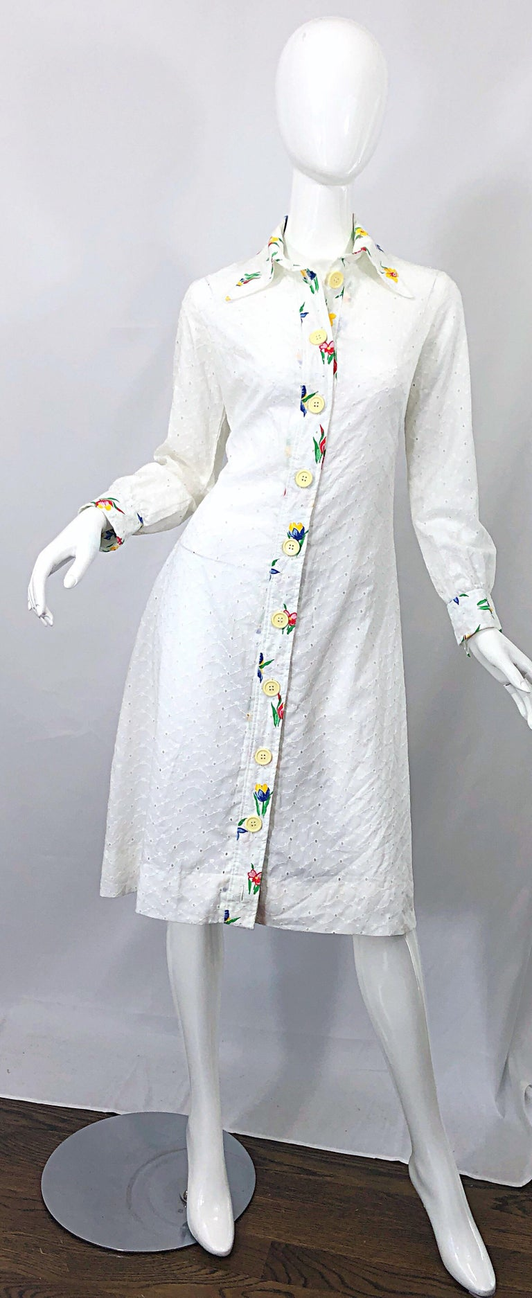 Chic 1970s JOSEPH MAGNIN white cotton eyelet embrodiered long sleeve shirt dress! Features a stark white color with embroidered flowers down the front center, collar, and sleeve cuffs. Vibrant colors of red, blue, yellow, green and orange. Buttons