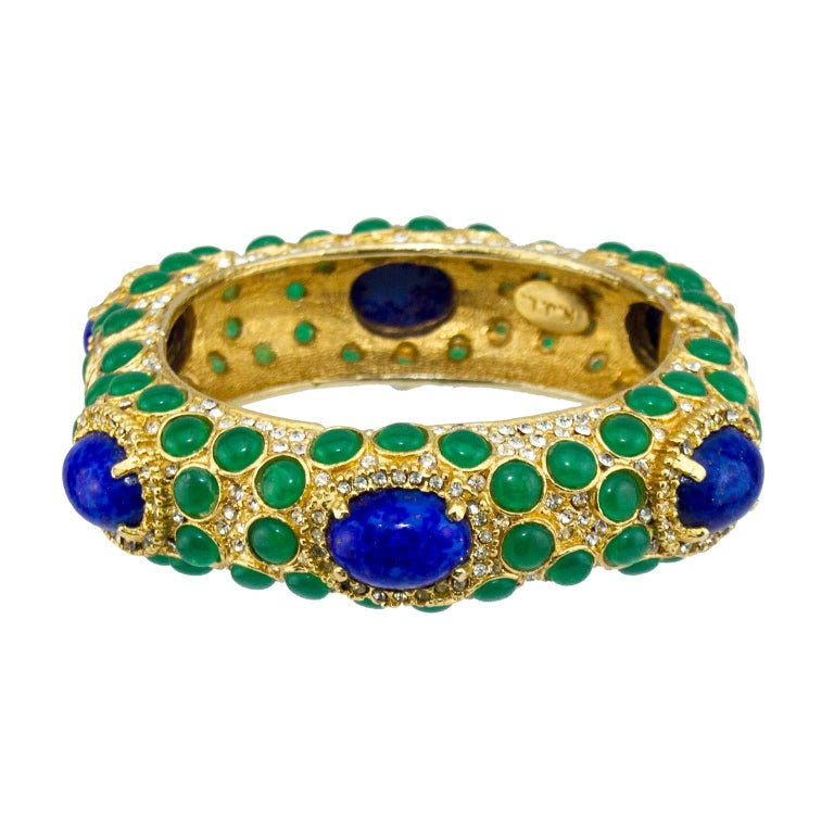 Vibrant 1970s Kenneth Jay Lane bangle. Gold tone metal embellished with tiny rhinestones and emerald green stones. Six large cobalt blue poured glass stones are featured in a four prong setting with more tiny rhinestones around them. K.J.L plaque on