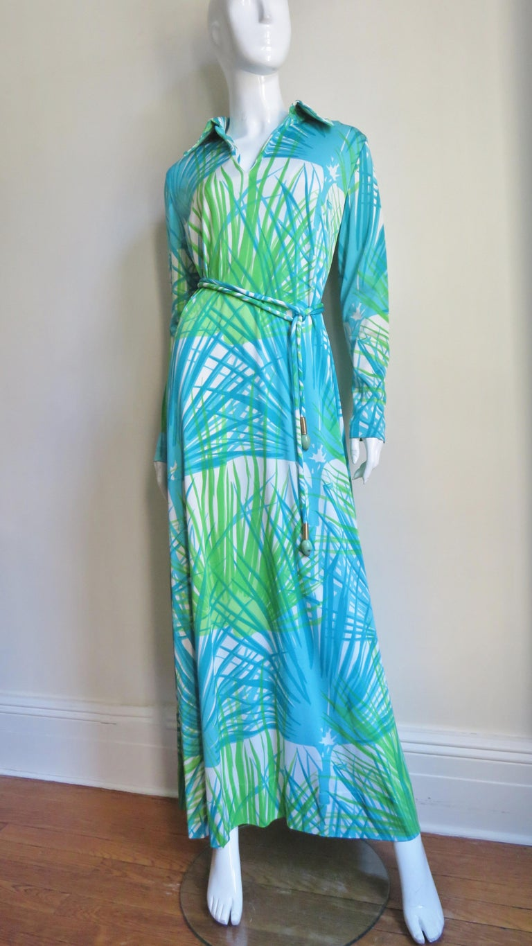 A great three piece jersey and silk set in an abstract grass pattern in blues and greens grass from La Mendola, Italy consisting of a maxi dress, tie belt and matching semi sheer silk over skirt. The dress has a collar V neck, 5 self covered buttons