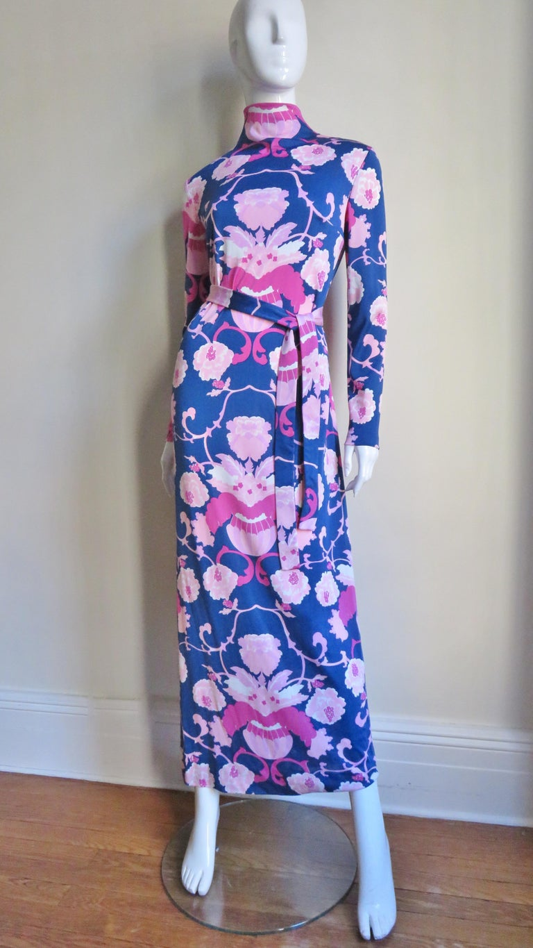 A 2 piece jersey and silk chiffon set in various shades of pinks on a blue background pattern of flowers and vases. The maxi dress comes with a matching tie belt and a silk chiffon over skirt in the same pattern.  The long sleeve dress has a stand