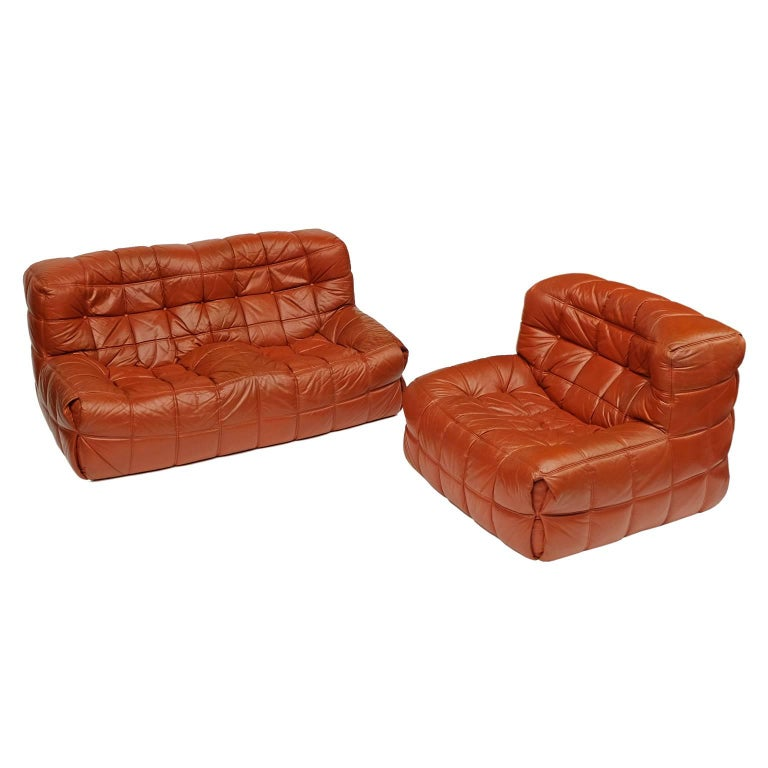 Two-seat sofa and matching chair designed by Michel Ducaroy for Ligne Roset, 1976.  Foam seating elements upholstered in stitched leather.  Ligne Roset labels.  Measures: Sofa H 75cm x W 160cm x D 100cm. Chair H 75cm x W 102cm x D 100cm.