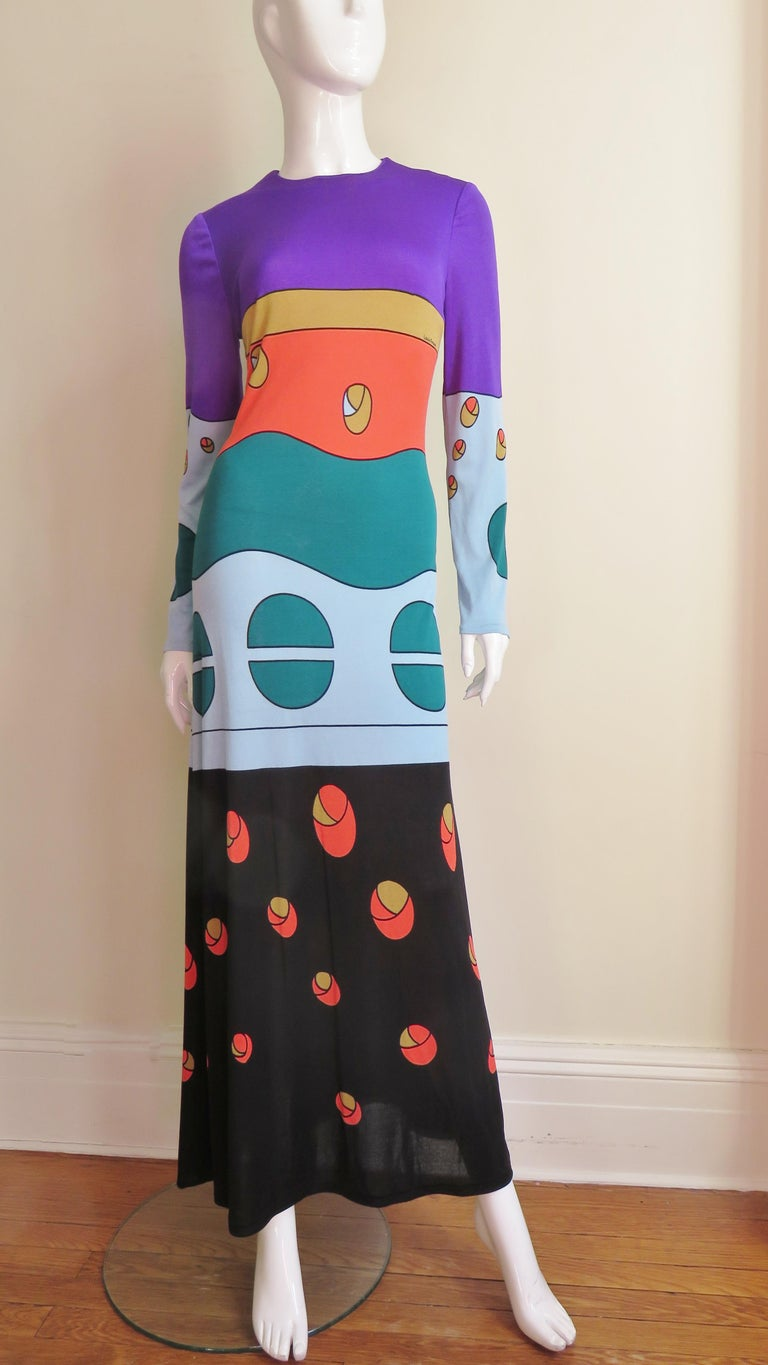 A full length long sleeved jersey dress by Louis Feraud with abstract shapes in greens, orange, blue, purple and black.  It is a simple rounded neckline long dress which skims the body flaring slightly at the hemline. It is covered in beautiful