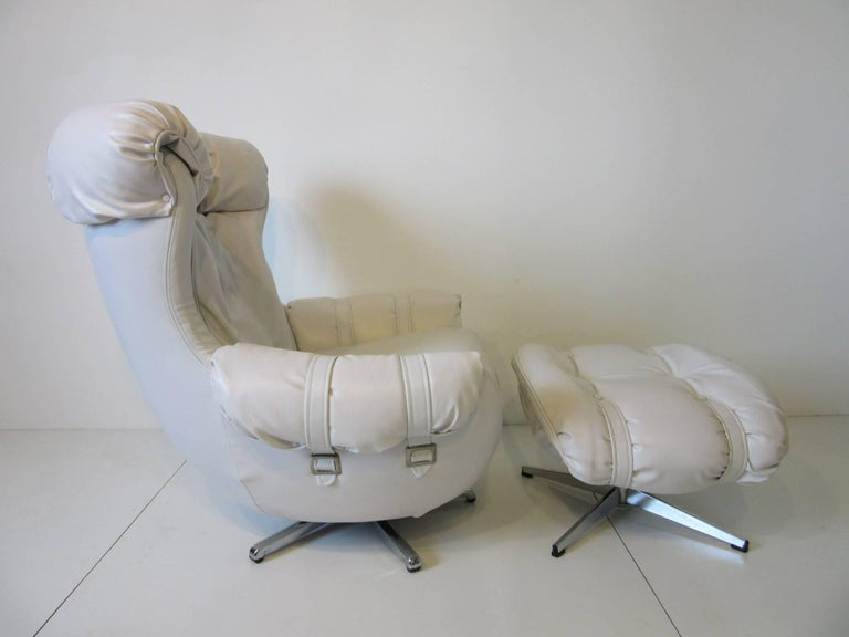 A pair of white Naugahyde swiveling and rocking lounge chairs with silver buckles and star bases and white straps set the style of the 1970s and Studio 54. Measurement for the ottoman is 28