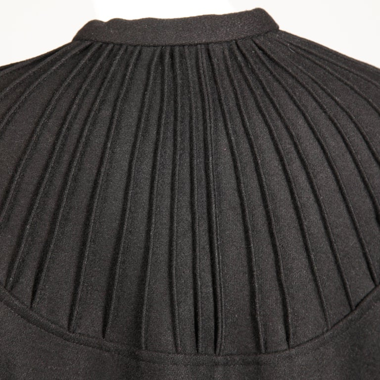 Heavy and warm vintage 1970s black wool cape coat by Luba Rudenko. This cape has top stitching around the neckline in a radial design and an ascot tie at the neck. It hooks in front with a single hook closure. Unlined. Will fit most sizes on account