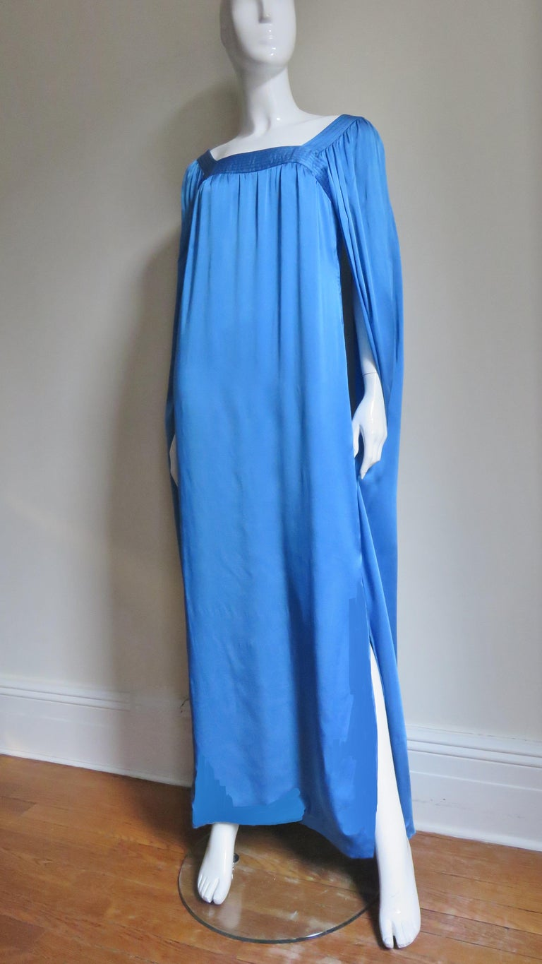 A beautiful blue silk charmeuse dress from Marc Bohan for Christian Dior Couture. The neckline is square, framed in rows of top stitching.  The body of the floor length dress is gathered onto the neckline and the angel sleeves emanating from the