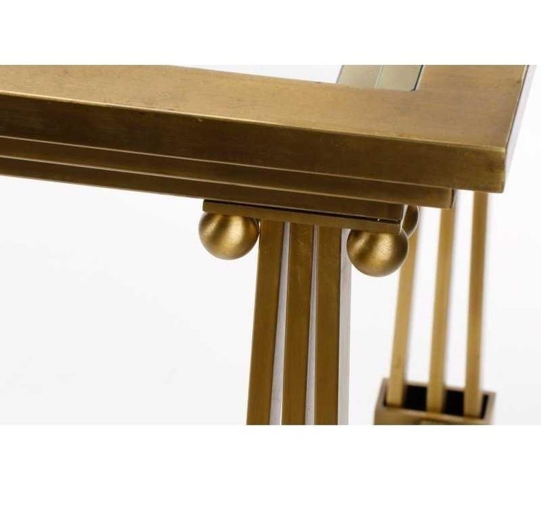 Architectural brass and glass dining table by Mastercraft, manufactured in the 1970s. The legs of this table have a nice columnar detail and glass insert that bring the whole design together. Brass with a beautiful lustrous patina and adds timeless