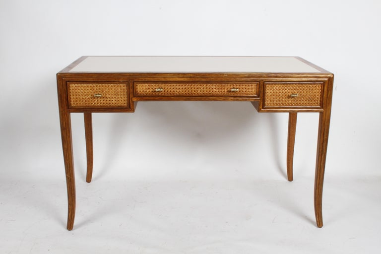 1970s McGuire furniture of San Francisco designed desk with splayed legs, caned panels and faux brass pulls. This elegant design, reminds me of T.H. Robsjohn-Gibbings designs for Widdicomb and Baker. Rattan frame with crème laminate top, frame to be