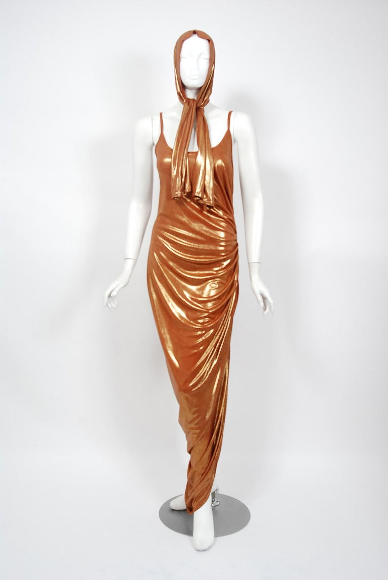 With its vibrant metallic bronze color and flawless styling, this 1970's poly-lurex dress has that disco chicness the 1970's were known for. The low-cut thin strap scoopneck is very flattering and effortless to wear. The one sided ruching is both