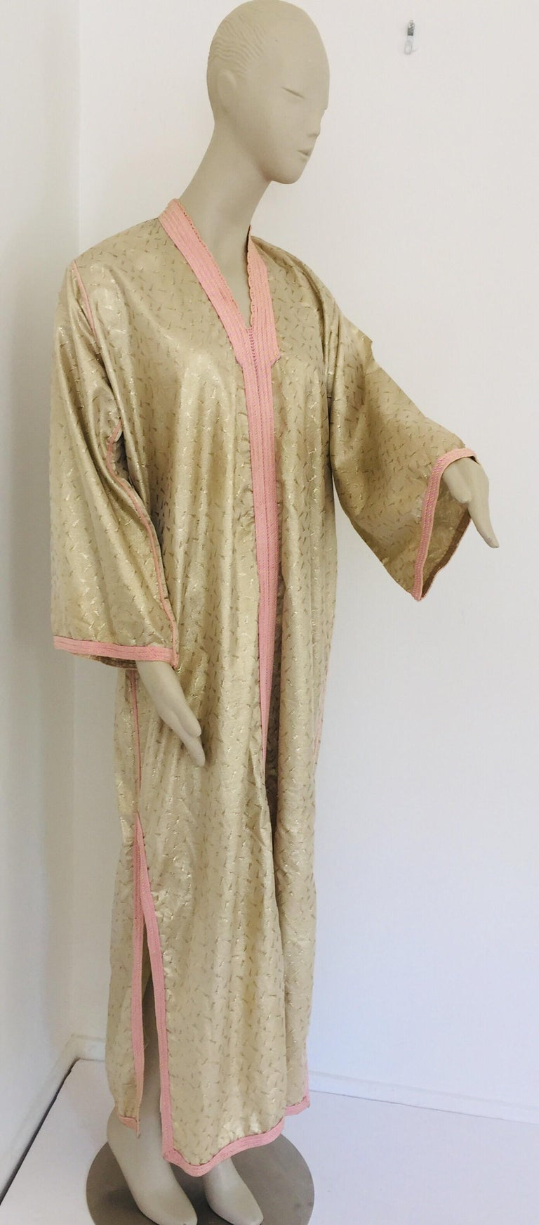 Moroccan evening or interior gold metallic brocade dress kaftan with pink trim. Handmade vintage exotic, 1970s metallic brocade caftan gown from North Africa, Morocco. The luminous gold metallic Moroccan caftan maxi dress is made in a subtle