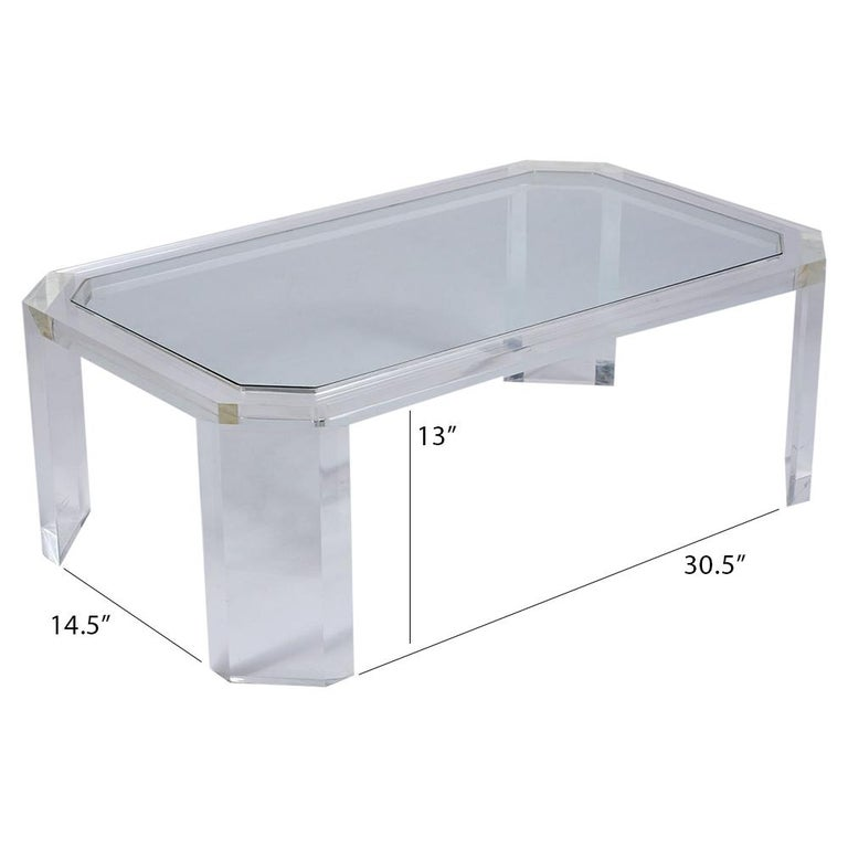 This Sleek 1970s Modern Lucite and Glass Cocktail Table features a unique octagonal top with glass insert and is raised by four double legs that are very stable/sturdy. This Mid Century Lucite Coffee Table would make a great addition to any home or