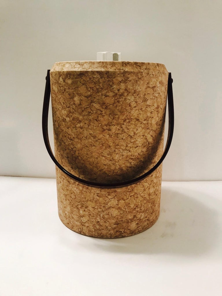 Chic 1970s acrylic ice bucket wrapped in cork design waterproof laminate. Tall cylinder form features a dark brown Lucite handle and clear Lucite lid fitted with stylized ice finial and a white acrylic interior. Indoor/outdoor use and easy to clean.