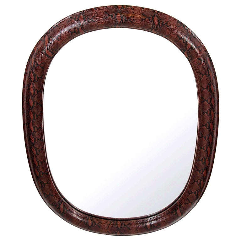 Stunning Mid-Century Modern rounded mirror with oval form. Wrapped in red and black snakeskin print embossed leather. Leather over hand carved wood with half round molded frame. In the style of Karl Springer.