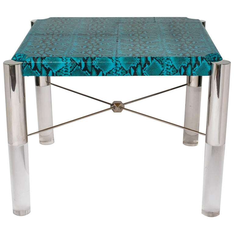 Get your game on with this stunning Hollywood Regency game table in vibrant turquoise leather with embossed python pattern. Square table with shield top design. Cylinder legs are comprised of gunmetal finish and solid Lucite. Fitted with X crossbars