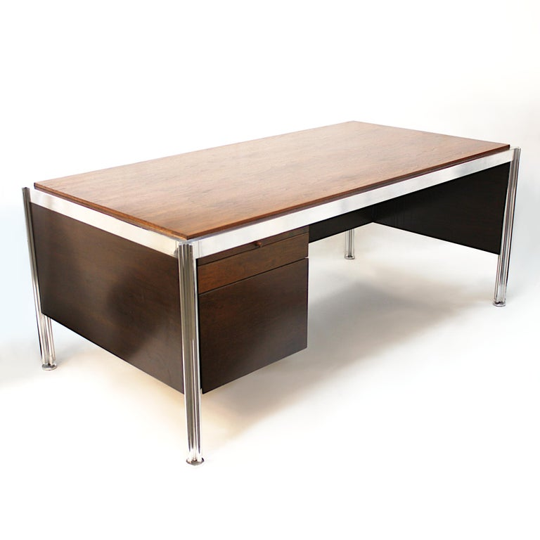 Amazing 1970s walnut and aluminum executive desk designed by George Ciancimino for Jens Risom Furniture. Desk features a sleek, Minimalist design, two drawers, two slide-out tablets, and unique, puzzle-shaped aluminum legs. Would make an impressive