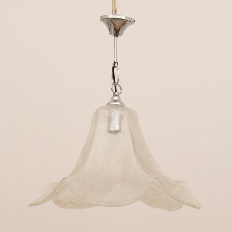 1970s white clear glass pendant hanging light with a polished chrome fitting. Manufactured in Germany by Hustadt Leuchten. The hanging light is formed by one piece of tulip shaped heavy glass with a chrome fitting, chain and ceiling cup. The light