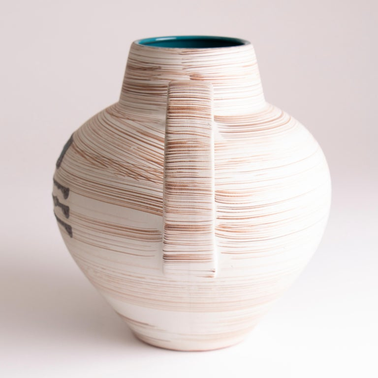 1970s jug vase from Carstens Tönnieshof, West Germany. The exterior is covered with thin brown horizontal lines with silver, raised, glazed lines and abstract squares over the top. The inside of each of the abstract squares is filled with a light