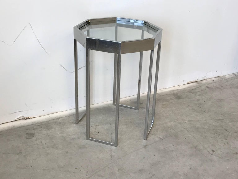 Listed is a stunning and unique, 1970s Milo Baughman chrome octagonal cocktail side table. Glass top. On two sides of the chrome top, there are two holes on each side (see photo 3)-- looks as if there were handles at some point in time. Buyer can