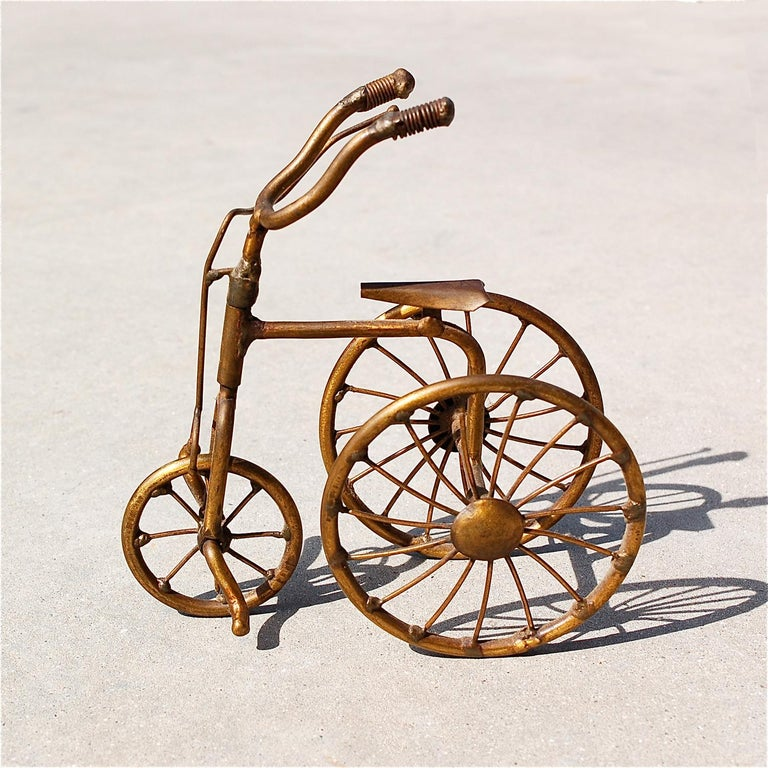 Miniature handmade brass tricycle by Belgian artist Daniel D'Haeseleer (1947). He studied at the Academy of Arts and started as a graphic artist. He later evolved to bas-relief sculptures and three-dimensional art. He masters different techniques