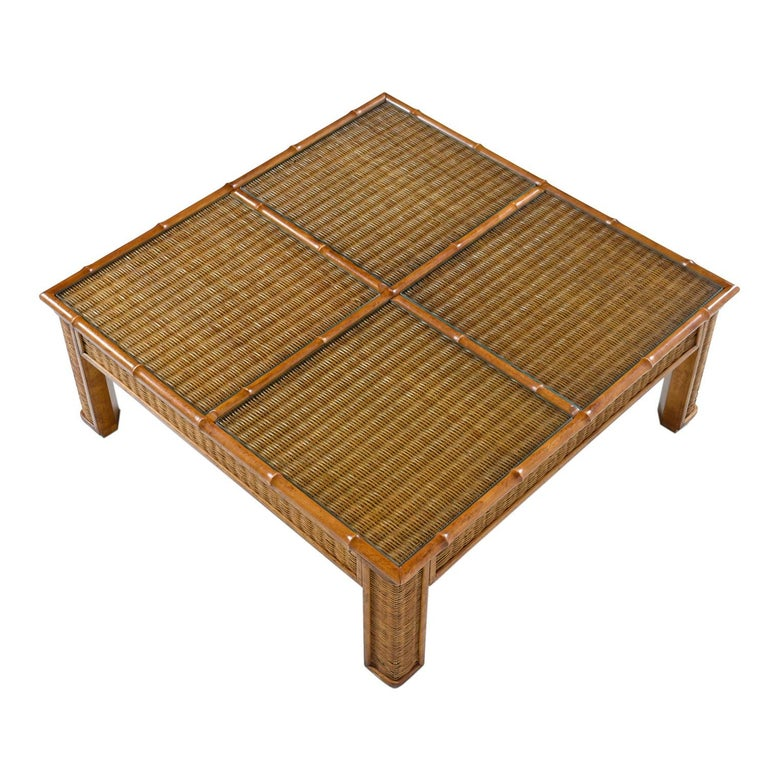 Vintage 1970s monumental boho wicker and rattan coffee table. Four in-set glass panels add a touch of elegance and enhance functionality. Constructed of wicker with four in-set glass panels and trimmed in robust rattan. The table is at once Bohemian