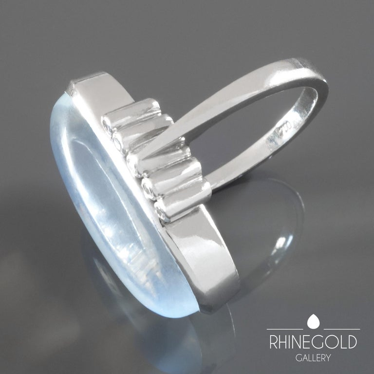 "1970s Modernist 17.5 Carat Moonstone Diamond White Gold Ring  18k white gold; moonstone (approx. 17.5 carats), 10 diamonds (approx. 0.2 ct. In total) Ring head 2.72 cm by 1.98 cm (approx. 1 1/16"" by 3/4"") Ring size: Ø 18.1 mm = EU 57 / US 8 / ASIA"