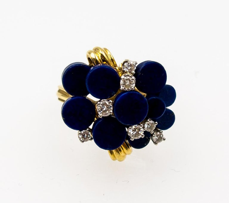 A delightfully amusing little cocktail ring straight out of the 70's, it's the Chinese game of Go in three dimensions, with its geometric shapes, alternating planes, and contrast between the deep blue lapis discs and the warm 18 karat yellow gold.