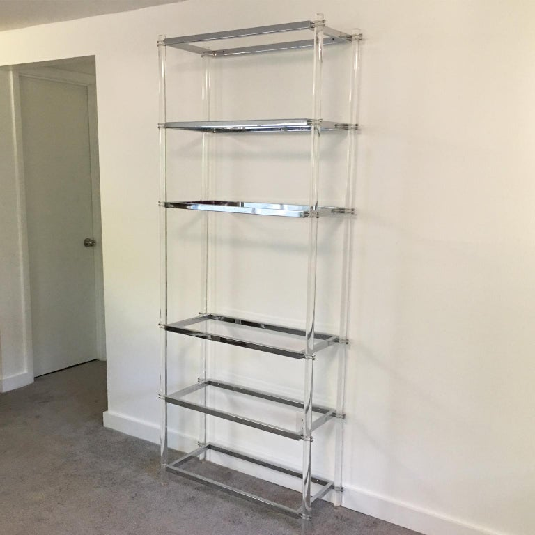 Striking 1970s modernist display shelf makes an ideal storage piece for a large variety of interiors. This elegant étagère or bookcase is sculpturally designed with crystal clear Lucite thick rods and chromed metal framing and accented with six
