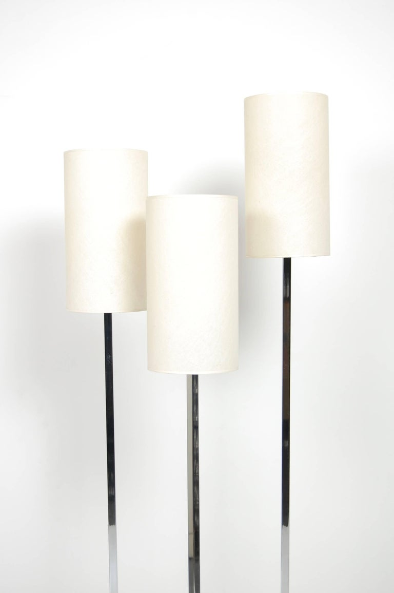 1970s three shade floor lamp with asymmetrical black cast iron base. The original off white shades are cylindrical and in excellent vintage condition. The upright light stems are chromed and the light is operated via a foot switch.
