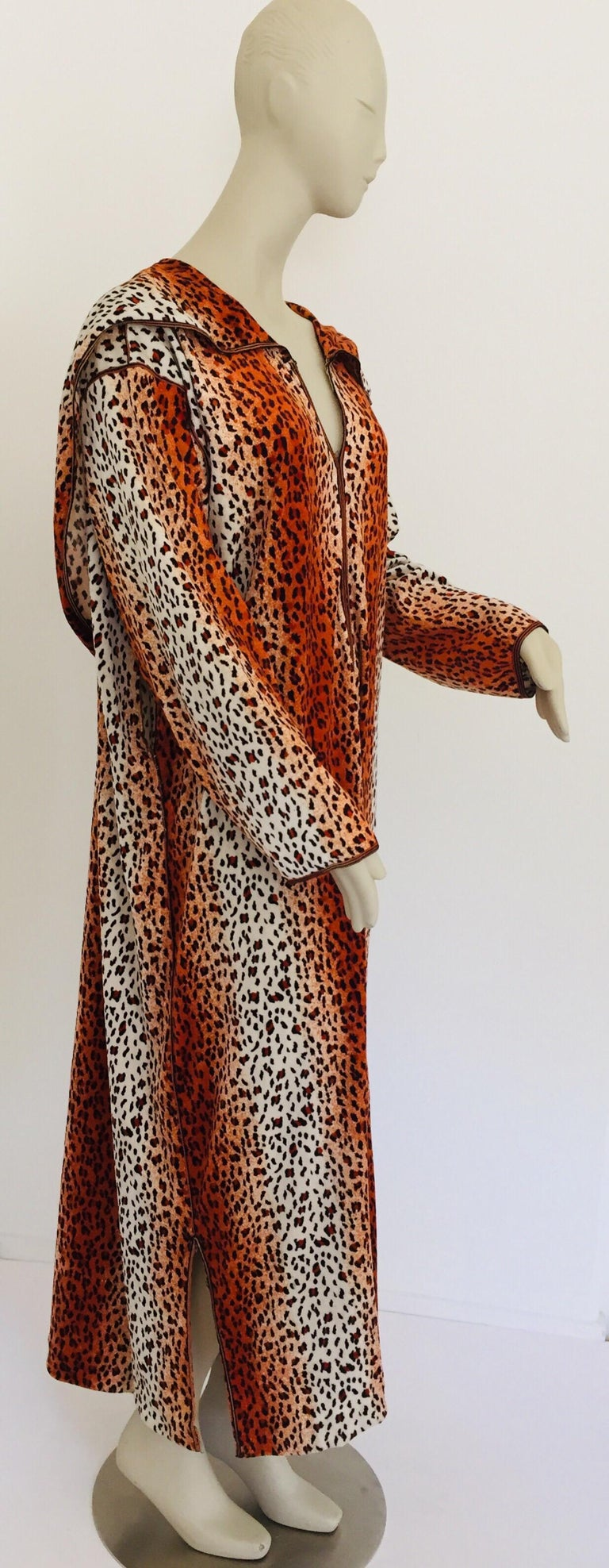 Moroccan animal print hooded caftan in light fabric with black trim embroidered, circa 1970s.  This light summery djellabah is crafted in Morocco and tailored for a relaxed fit, features a traditional neckline, embellished sleeves and vented sides.