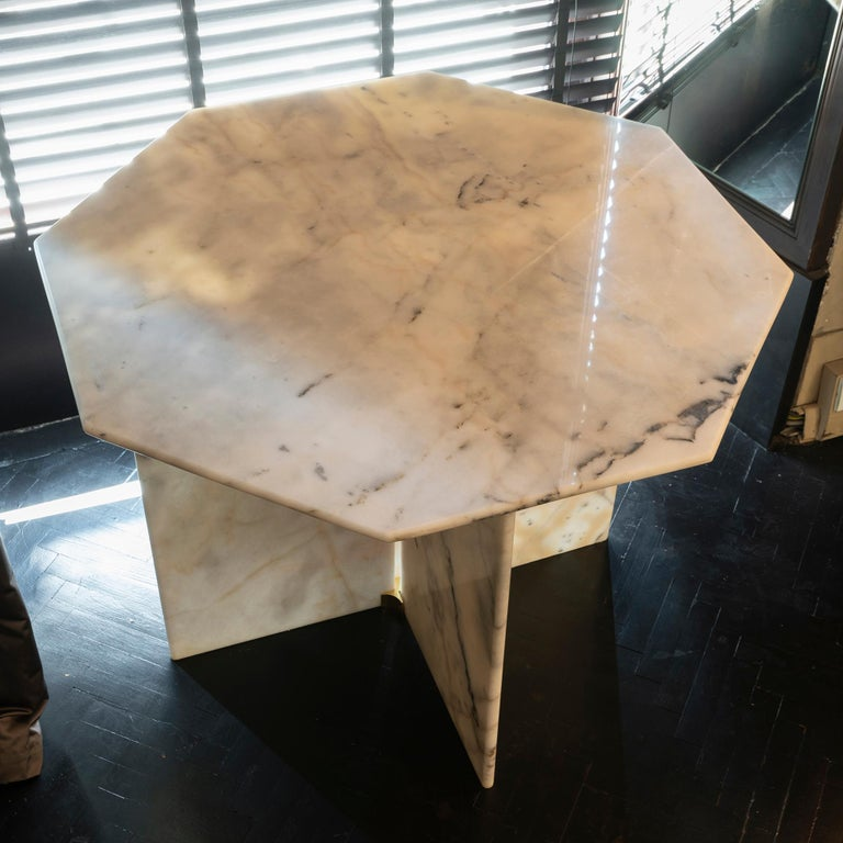 1970s Italian table in white Arabescato Cervaiole marble, octagonal top, the base is made up of four marble slabs held together by a pair of brass elements, the table is completely dismantled for traveling.
