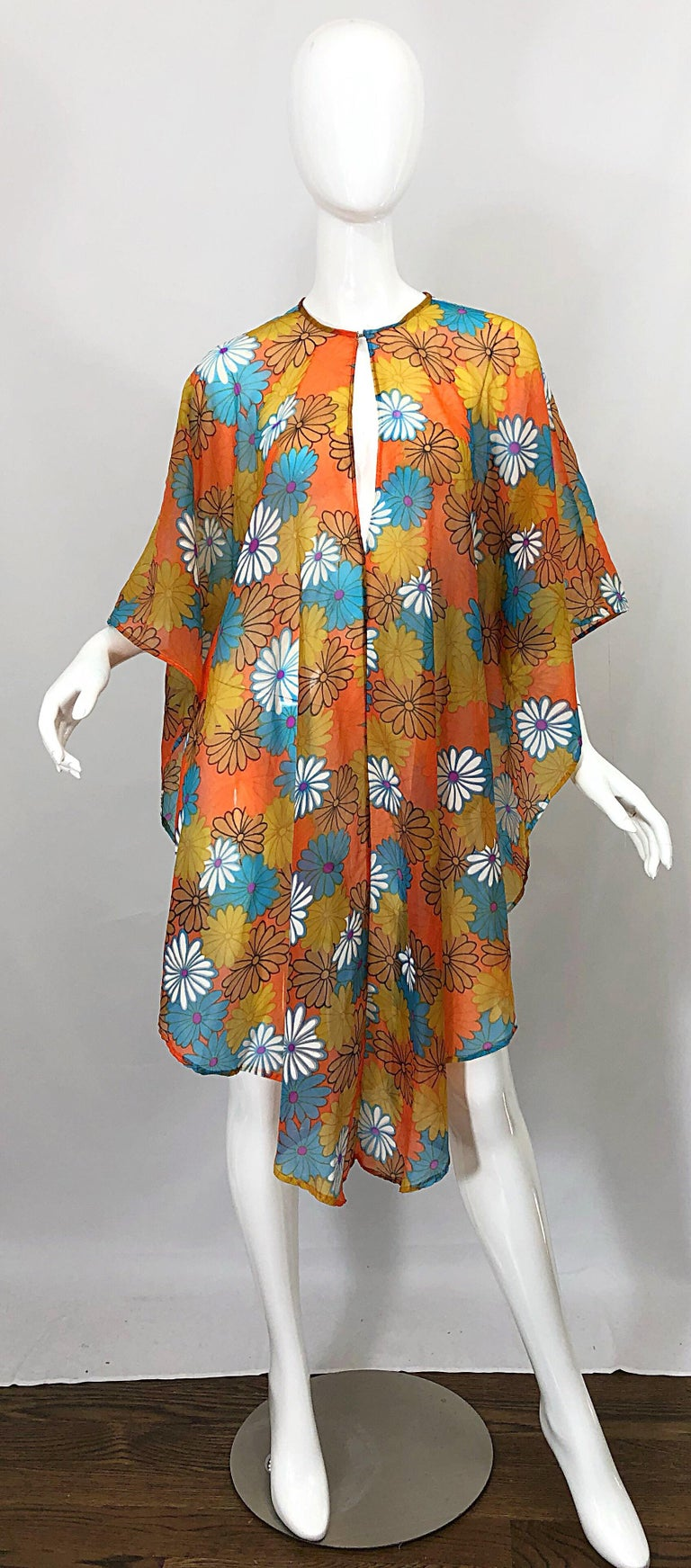 Incredible vintage 70s semi sheer chiffon flower print poncho top! Features vibrant colors in various shades of orange, blue, purple and white. Soft nylon chiffon is both soft and durable. Keyhole at neck can be worn either forward or on the back.