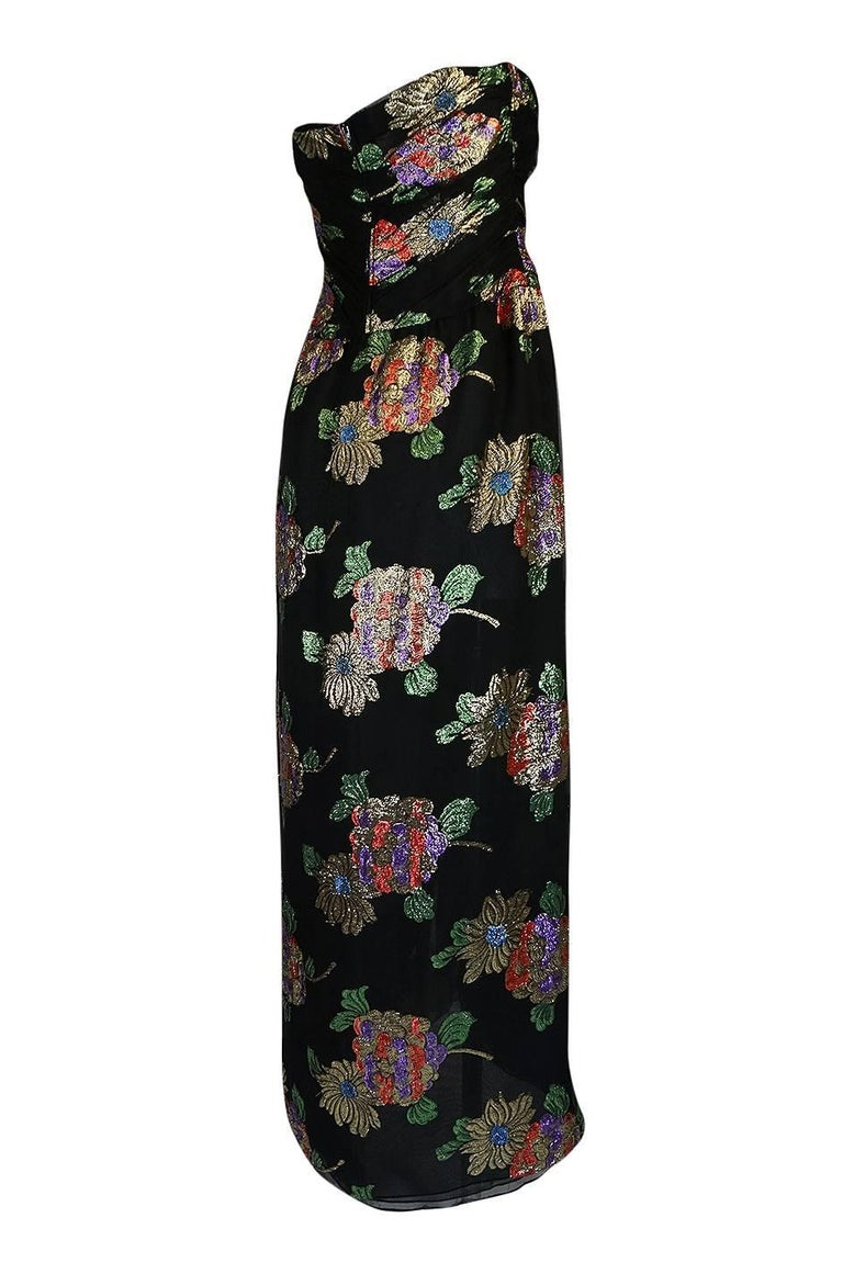 This is a stunning strapless silk and metallic dress by Oscar De La Renta. The floral pattern that runs over the black silk chiffon is so vibrant and beautiful. My photos do not begin to do the colors justice. These are bright metallic lame thread