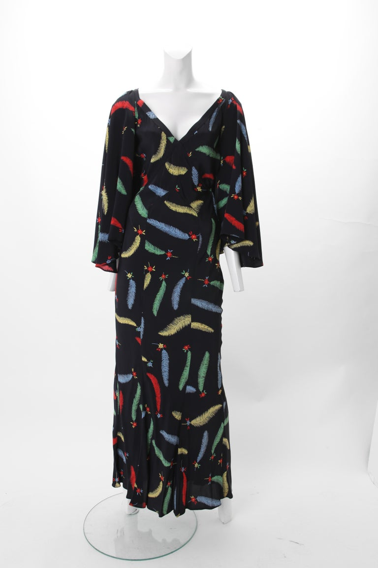 1970s Ossie Clark Celia Birtwell Print Maxi Gown; V-neck empire bodice with flared sleeves; Open back with criss-cross panels w/ metal hoop fastening; side zipper closure. Polychrome leaf and flowerhead print on black ground.