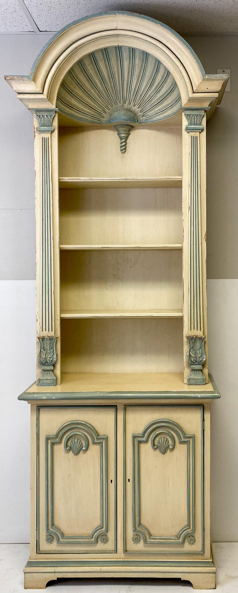 This is a pair of painted grotto inspired carved shell bookcases. They are American and date to the later part of the 20th century. They are unmarked and there is wear to the ivory and blue painted finish.