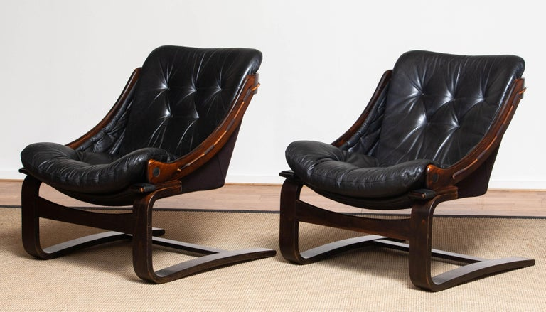Original set of two Scandinavian lounge chairs designed by Ake Fribytter for Nelo Möbel in Sweden. Both are upholstered with black leather and dark brown linen. Overall in good condition.