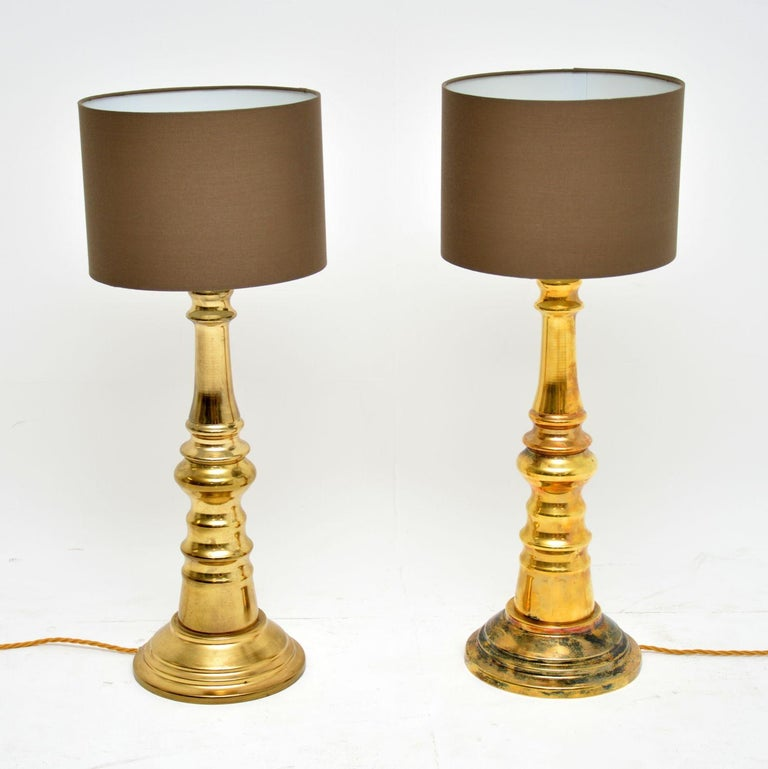 A stylish and impressive pair of vintage brass table lamps. These date from the 1970s, they are in good overall condition. They are clean and sturdy, with some areas of tarnishing to be seen, mostly on the base of one lamp. We have had these